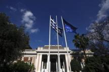 A Greek national flag and a EU flag wave outside the office of Greek PM Samaras in Athens